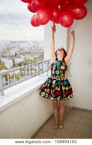 Young red-haired woman looks upward at bunch of red balloons that she holds in hand standing at balcony of highrise building.