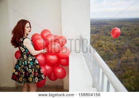 Young smiling red-haired woman holds in hand bunch of red balloons and leaves one to fly standing at balcony of highrise building.