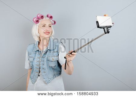 Good idea. Overjoyed senior beautiful woman smiling and taking selfie while standing against isolated gray background.