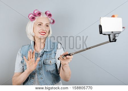 Hi people. Amused senior pretty woman using headphones and taking selfie while standing against isolated gray background.