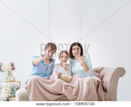 AIDS campaign. Pleasant nice good looking family sitting on the sofa and wearing red AIDS awareness ribbon while looking at you