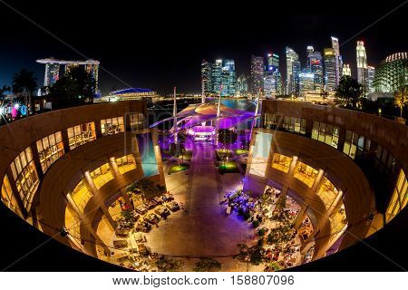 Night scene of the Esplanade at Marina Bay with the Singapore skyline in the background. The area comes alive at night with vibrant shows and attractions. Fisheye view.