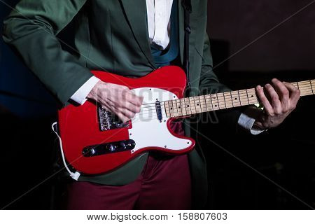 Guitarist playing red electric guitar in retro style clothes at concert