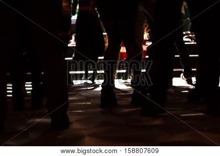 Party dance-floor with legs and feet of dancing people in concert lights