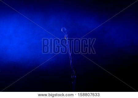 Singing microphone on stand in blue lights at concert
