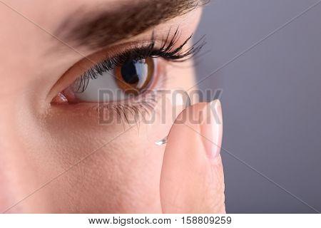Woman putting contact lens in her eye, closeup