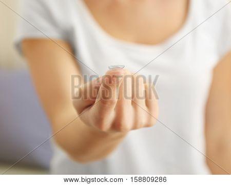 Woman holding contact lens, closeup