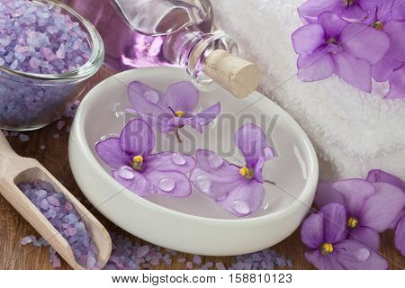 Floating violet flower in water aromatic essential oil sea salt soft towel and on wooden background