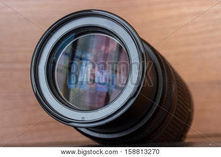 zoom lens of the reflex camera on the wooden background