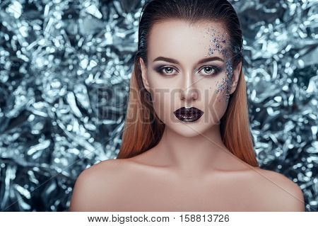 Beautiful young woman with evening shimmering makeup on christmas background looking in camera. people, beauty, fashion, holiday and magic concept.