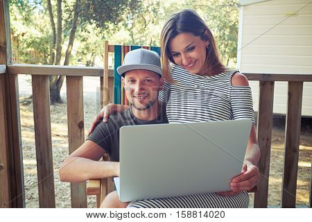 Close-up of young couple who is sitting together on a summer beach armchair and looking at the screen of a laptop