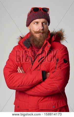 Portrait of a serious man wearing red winter jacket with mustache and beard with intense look to the side