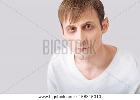 Fixed gaze. Serious thoughtful young man wearing a white pullover and looking at you while standing against the grey background