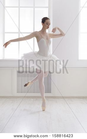 Classical Ballet dancer side view. Beautiful graceful ballerine practice ballet positions in tutu skirt near large window in white light hall. Ballet class training, high-key soft toning.