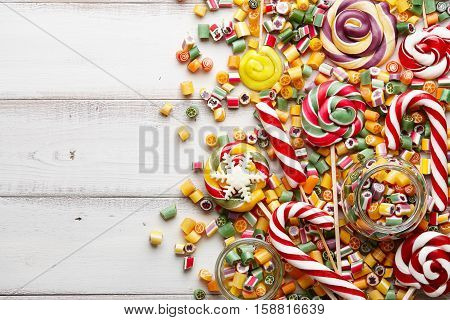 Colorful lollipops candy canes and sweet candies mix on white wooden background