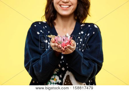 Young cheerful beautiful brunette girl in cosy knited sweater smiling with handful of confetti over yellow background. Copy space.