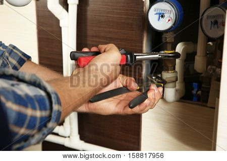 Hands of plumber using wrenches while repairing pipes, close up view