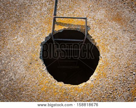 Abstract manhole in concrete wall with stairway do down