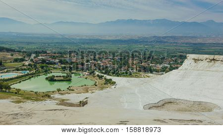 Pamukkale city and travertine terraces panorama with turquoise pool at front, Pamukkale, Turkey