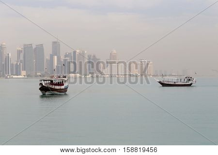 A misty morning in Doha, Qatar, in  2016, fades the towers of the Dafna business district behind the moored dhows.
