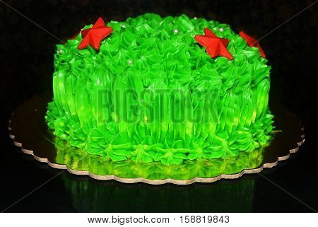 Christmas cake with green sugarpaste and red stars on black background