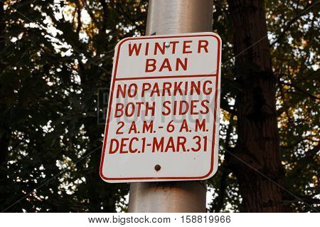 Parking ban in winter time road sign on roadside in front of trees.