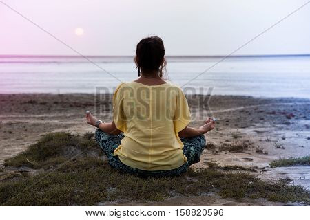 Girl Meditating At Sunset. Sits Back, Looks At The Sun