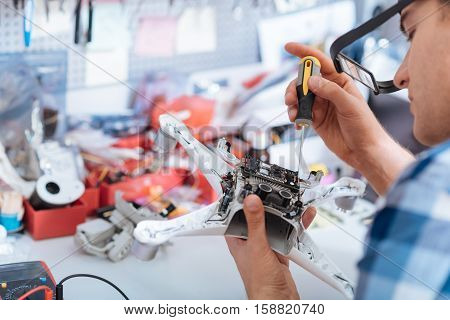 Technology and service. Concentrated young handsome man repairing drone detail and using screwdriver while sitting in a workroom.