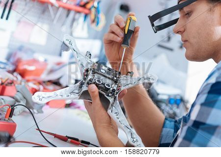 Service and technology. Handsome young delighted man repairing drone while using screvdriver and sitting in a workroom.