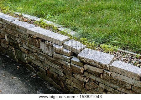 Granite wall made of bricks and fresh lawn grass shot with place for text on a sunny day.