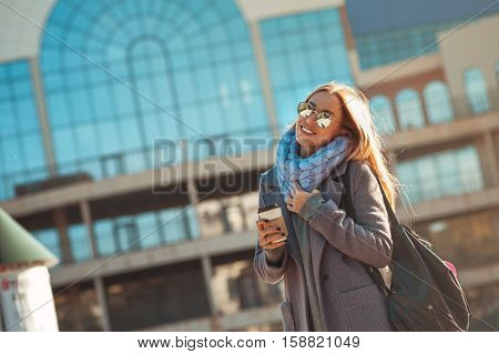 Great weather today for walk. Beautiful young blonde woman holding coffee cup and walking outdoors with smile on her face. Sunny day, happiness, coffee break, enjoying.