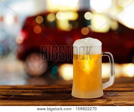cold glass mug of beer with foam on the background of the street
