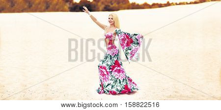 Beautidul smiling lady dancing Belly dance in the sands desert. colourful dress