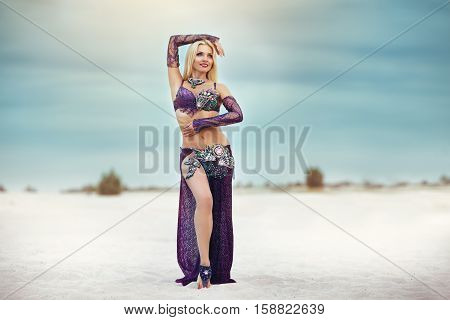 Beautidul smiling lady dancing Belly dance in the sands desert.