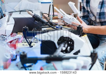 Solve the problem. Close up of hardworking mans hands repairing details of drone while holding them and using soldering iron.