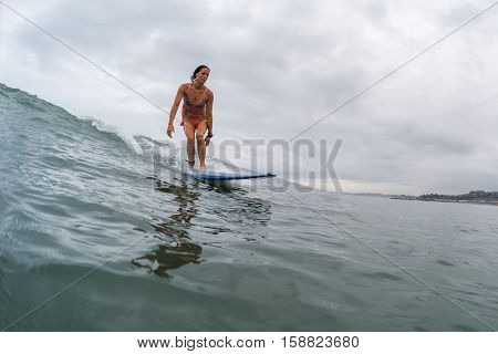 BALI, CHANGGU - NOVEMBER 25 2016: Young lady surfer catching the wave in the ocean