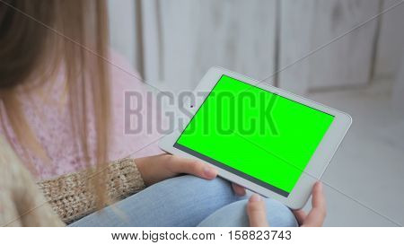 Woman using horizontal tablet computer with green screen. Close up shot of woman's hands with pad. Technology and internet concept