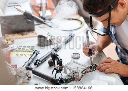 Doing it to death. Hardworking young concentrated man soldering drone details attentively and using soldering iron while working.