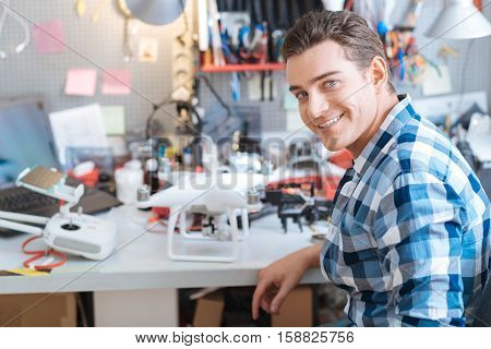 Smart and creative. Portrait of young handsome delighted man working with drone while sitting in the cabinet and smiling.