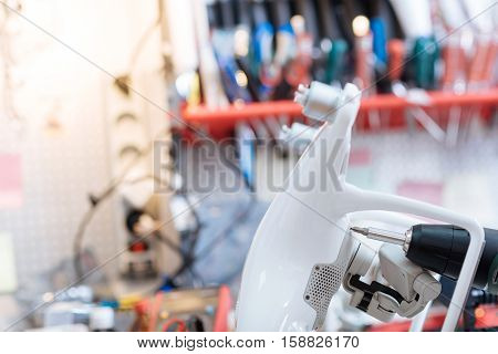 Attentive work. Close up of a process of drilling drone mechanism while repairing in and spending time in a workroom.
