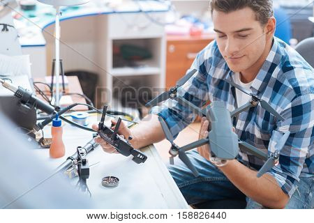 Way to success. Young joyful smart man putting together drone propeller and using other details while holding the remote controller.