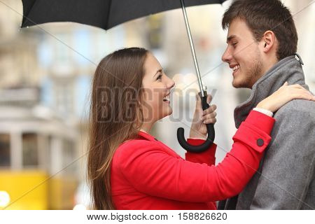Side view of a couple encounter in the street under an umbrella in a rainy day