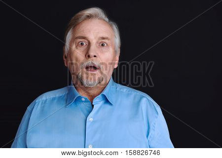 Be shocked. Closeup portrait of an elderly man looking wondered in full disbelief with wide opened eyes and mouth standing isolated on black background