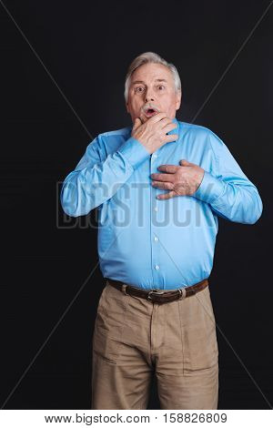 Feeling hopeless. Grey-haired man standing shocked with wide opened mouth and eyes holding one hand on the beard and another one on the breast wearing smart casual clothes
