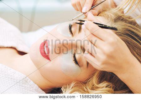 Master makes eyelash extension procedure on beautiful blonde woman