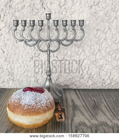 Traditional Jewish sweet donuts, menorah and other symbols for Hanukkah holiday. Selective focus. Image toned for inspiration of retro style