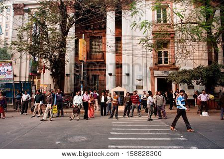 KOLKATA, INDIA - JAN 13, 2013: Pedestrians in a crosswalk waiting for the moment to cross the road on January 13, 2013 in India. Kolkata metropolitan area is spread over 1886.67 km2.