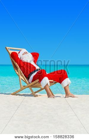 Christmas Santa Claus lounge in wooden deckchair at ocean tropical sandy beach - New Year travel destinations vacation in hot countries concept vertical seascape