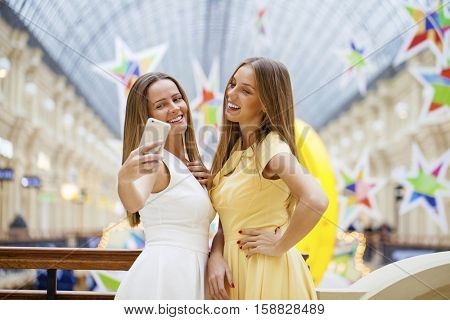Two Beautiful smiling women take a picture of herself with a smart phone. Selfie, shop indoors