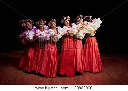MOSCOW, RUSSIA - MAY 21, 2016: Girls in red skirts, embroidered white blouses and with wreaths on their heads dance Russian folk dance during concert of dance studio Firebird in Bogorodskoe.